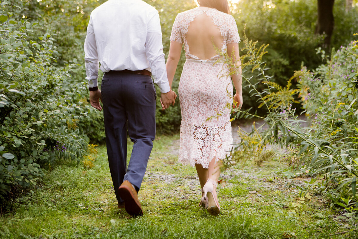 Couple holding hands walking through nature in Buffalo, New York