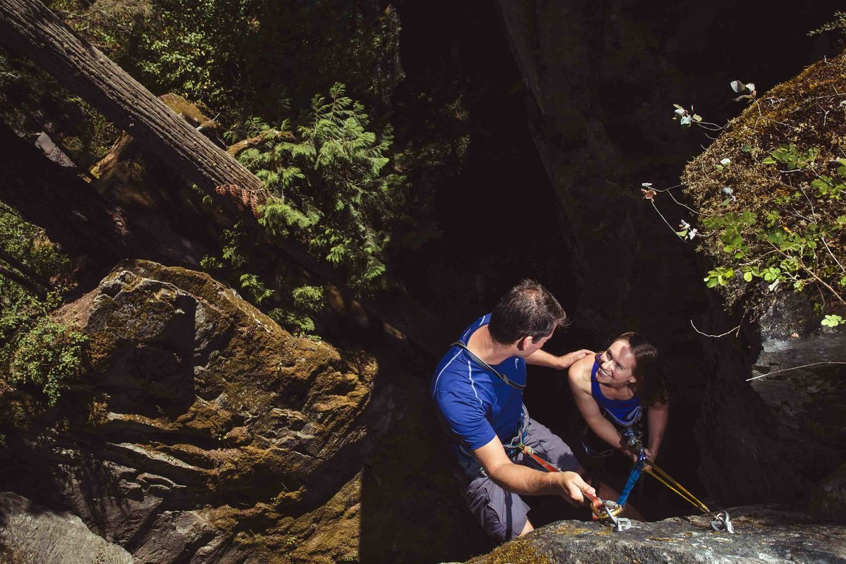 couple rock climbing during engagement session