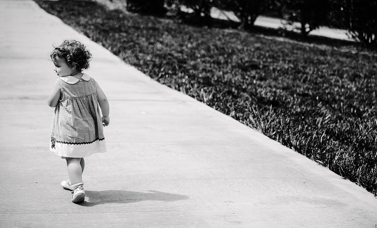 charlotte documentary photographer creates an artistic image of a toddler walking down a road