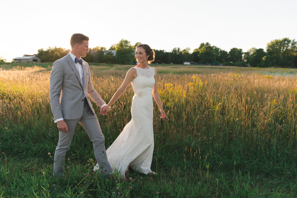 Bride and groom walking in tall grass at sunset at Strathmere in Ottawa