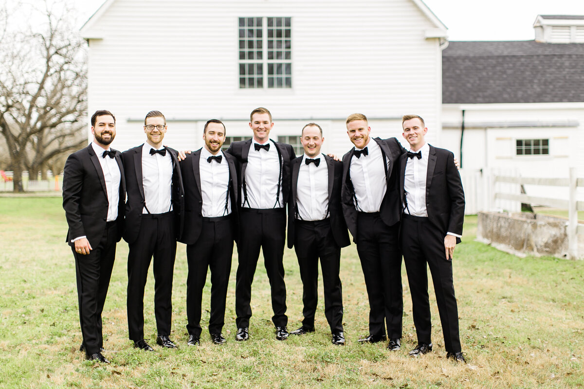 A group of groomsmen standing in front of the dairy barn at the Grand Texana