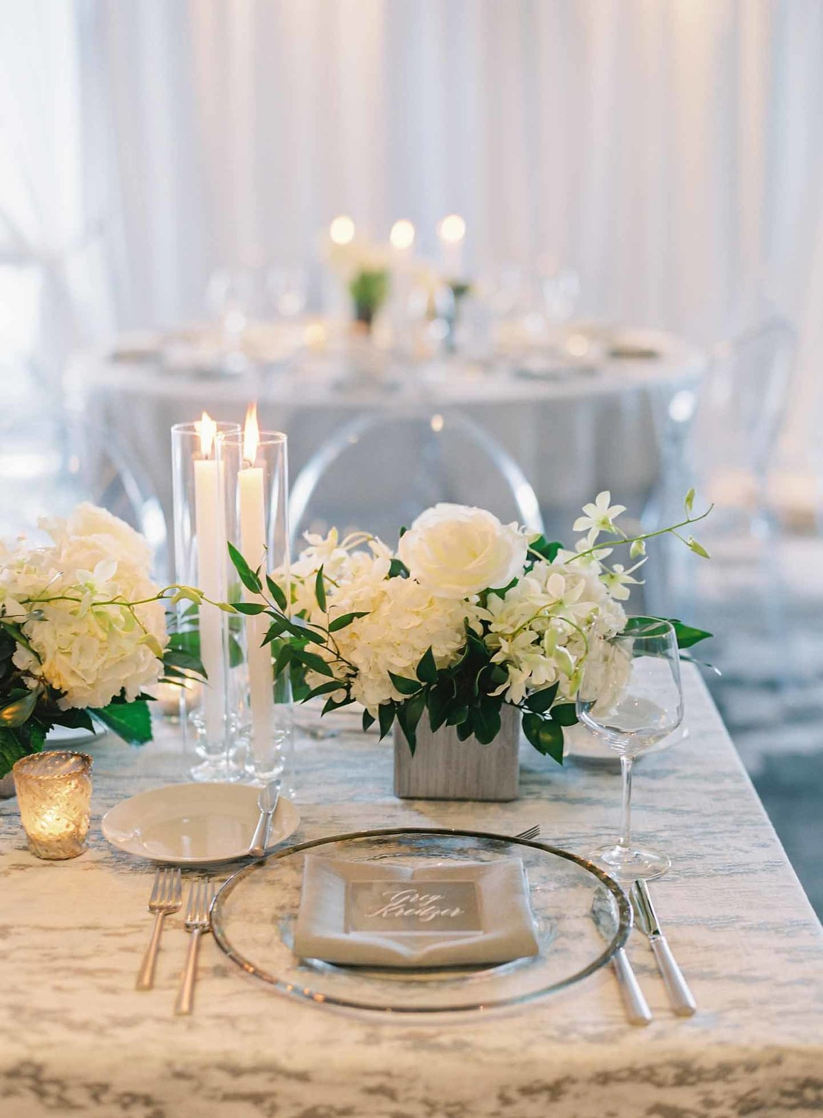 Sliver and white long low floral arrangements and taper candles line these long tables.