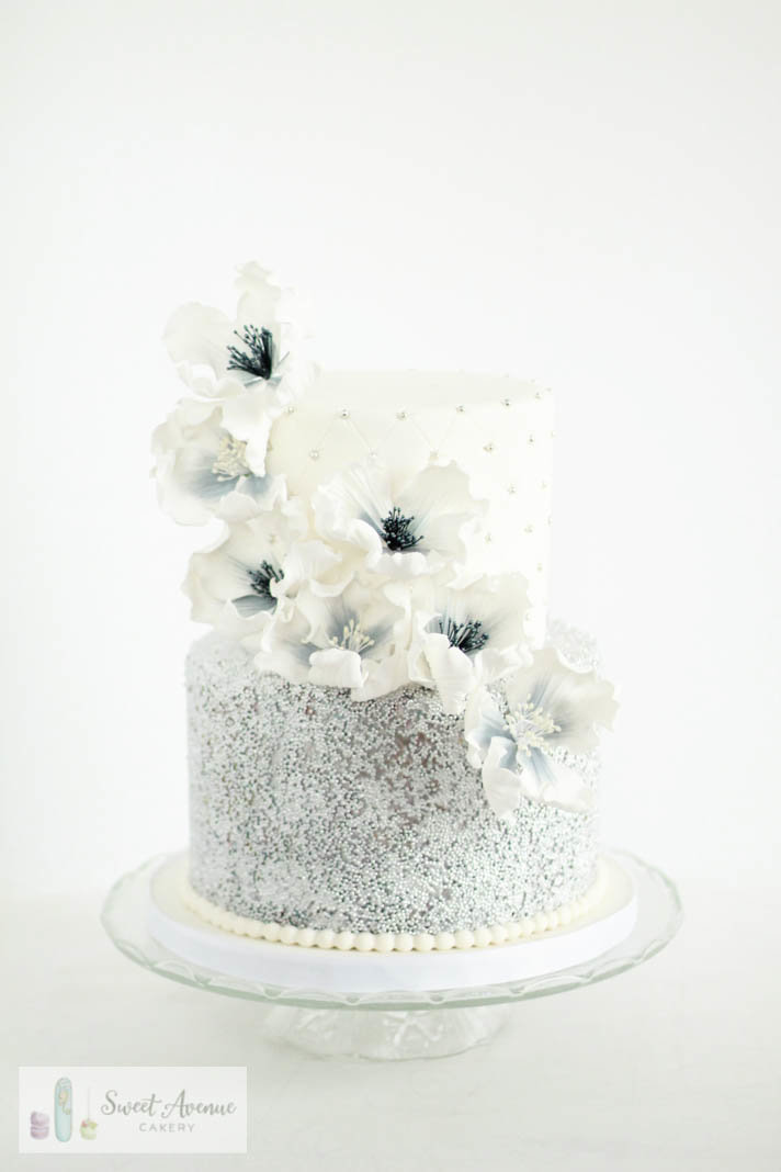 white and silver sequin wedding cake with cascading flowers