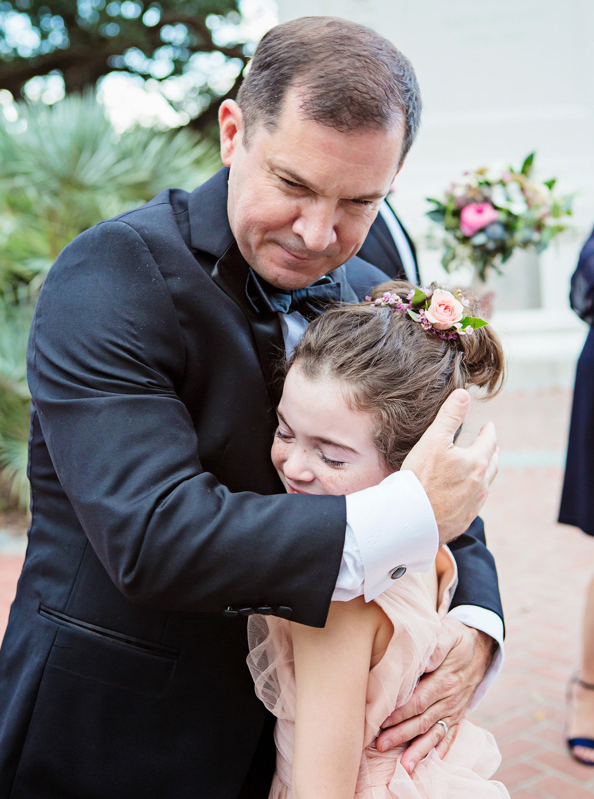 flower girl hugs new orleans groom after wedding ceremony