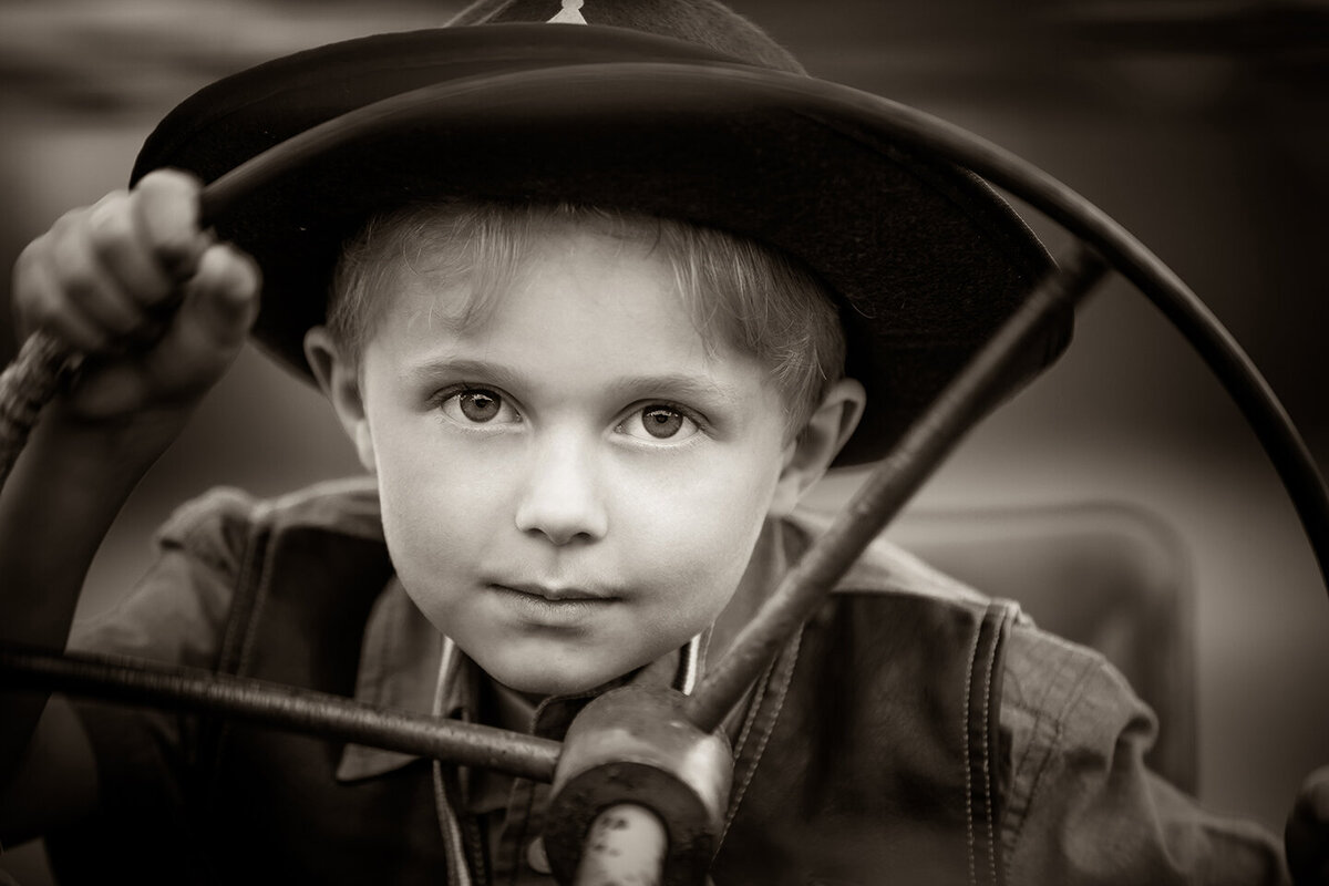 black and white picture of boy in hat driving old tractor, hand on steering wheel, family pictures in billings mt.