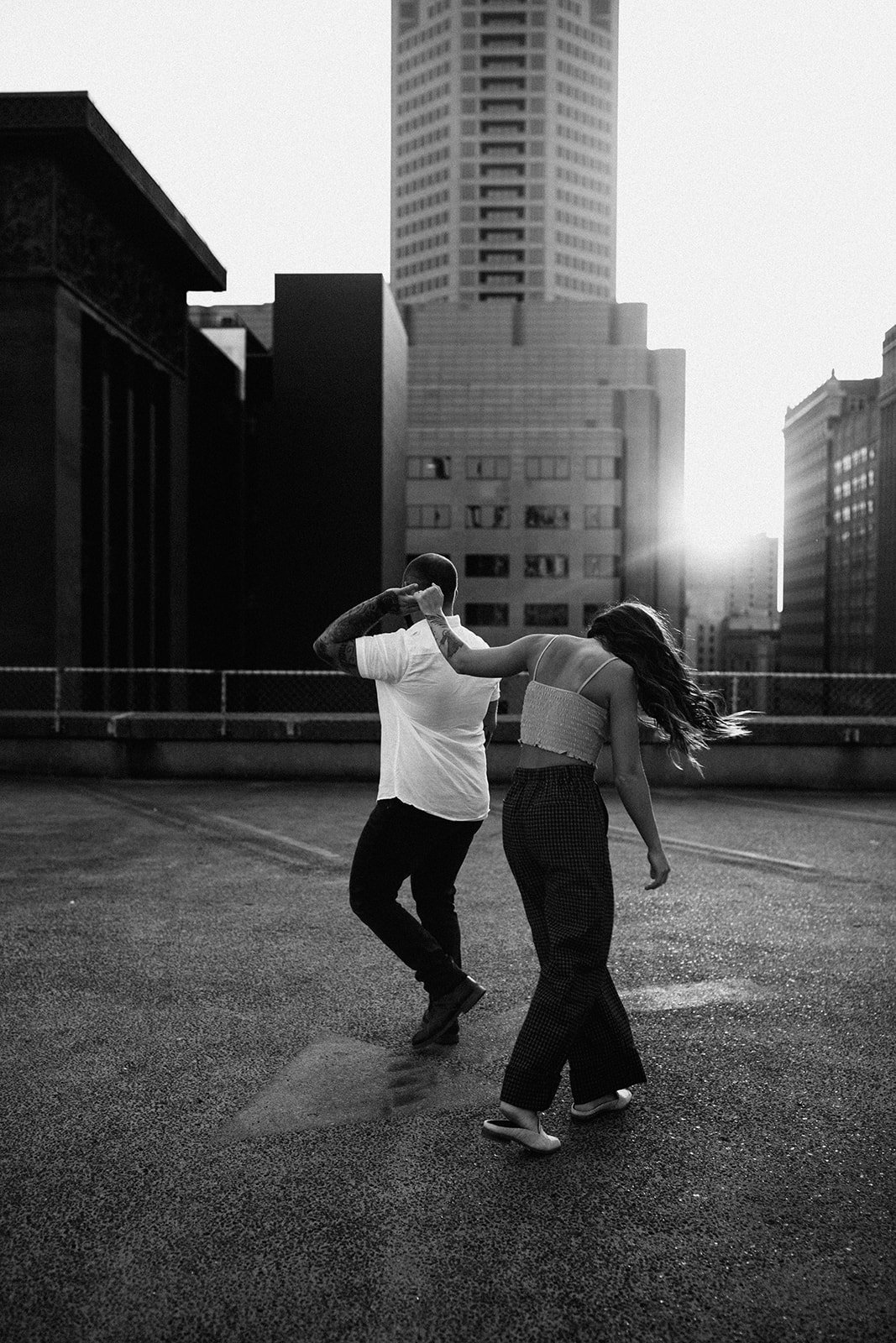 A black and white photo of a couple skateboarding on a rooftop.