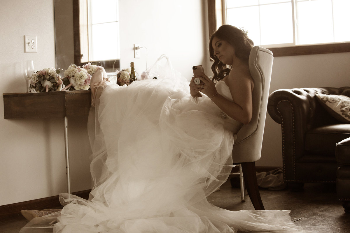 bride in bridal room selfie at blue haven, feet up on counter.