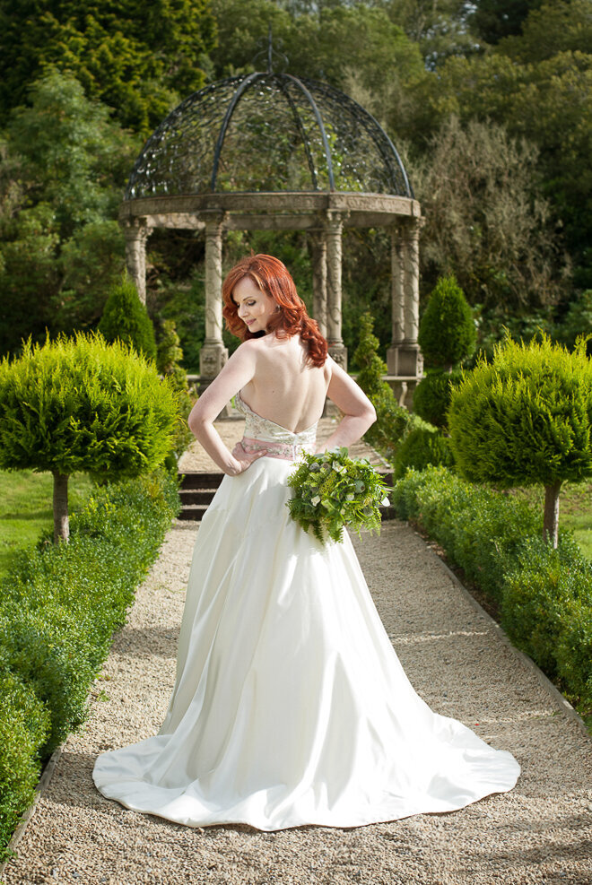 bride with long, silky, red hair wearing a ballroom style wedding dress with beaded bodice looking over her shoulder while holding a green wedding bouquet in the gardens of Ballyseede Castle, Kerry