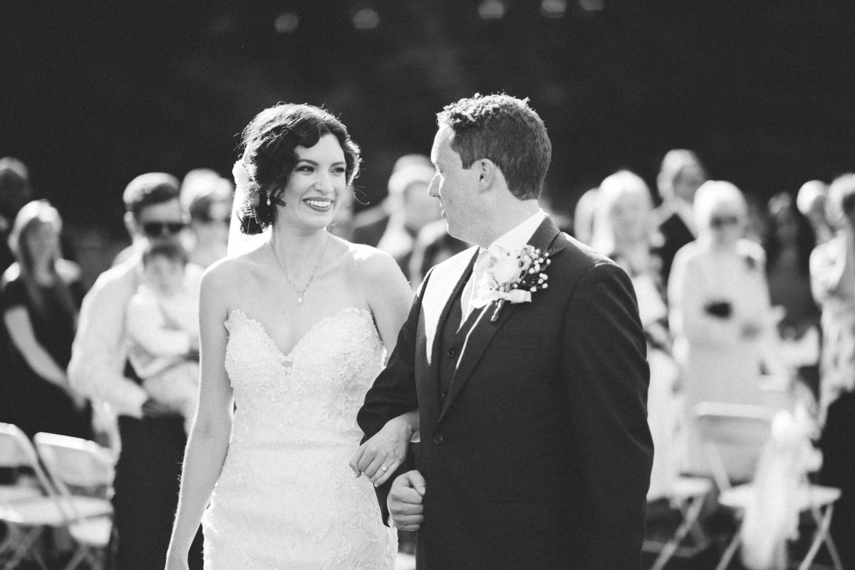 black and white groom and bride photo walking down the aisle