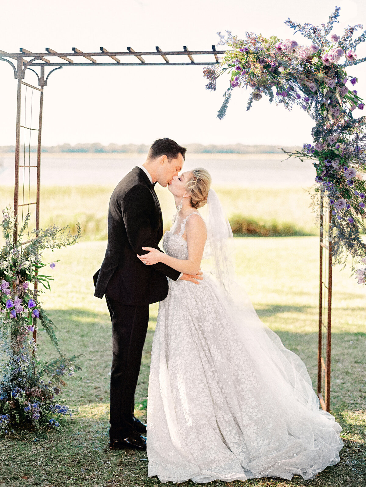 bride and groom kissing at altar of outdoor ceremony at Lowndes Grove Charleston wedding