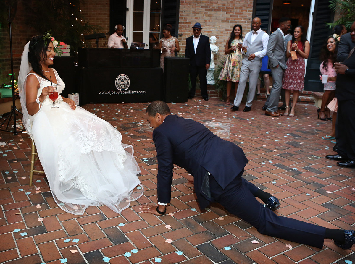 nola groom crawling across the brick to his bride for the garter toss