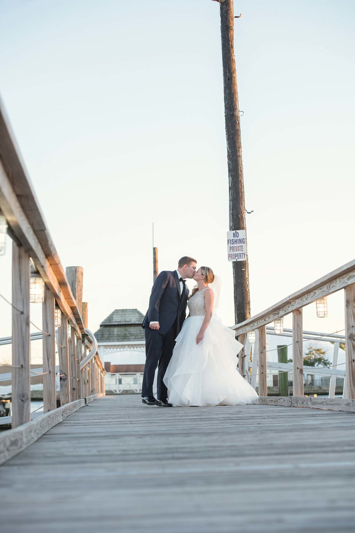 Bride and groom kissing at the docks of Bridgeview Yacht Club