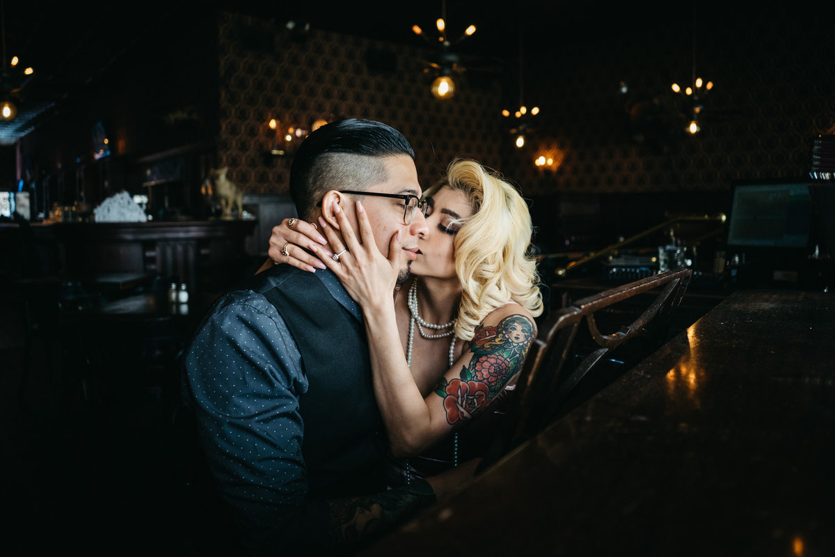 Blonde woman kissing her fiancé while he plays the piano.