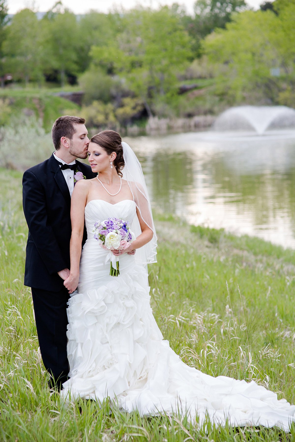 bride and groom in green field in denver