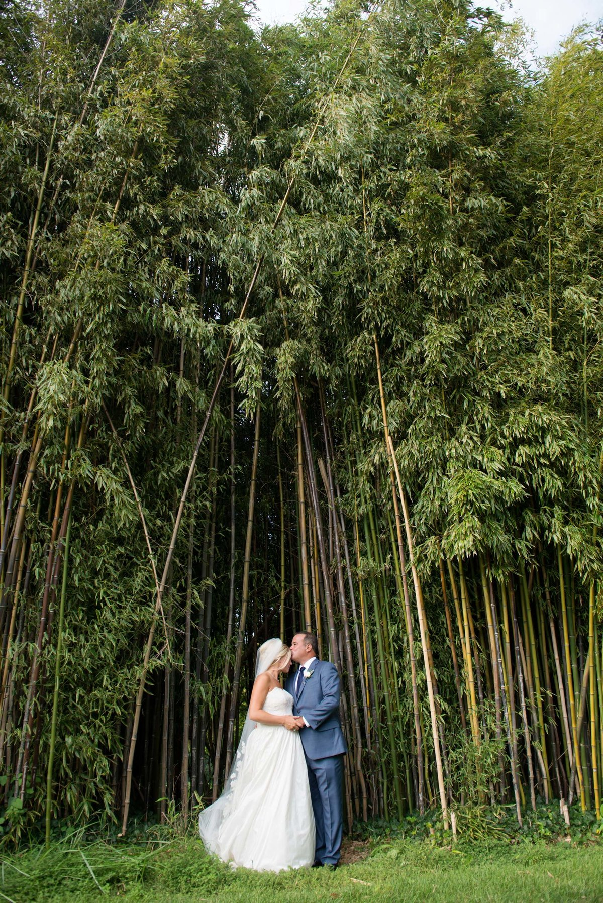 Bride and groom kissing in from of trees at Huntington Crescent Club