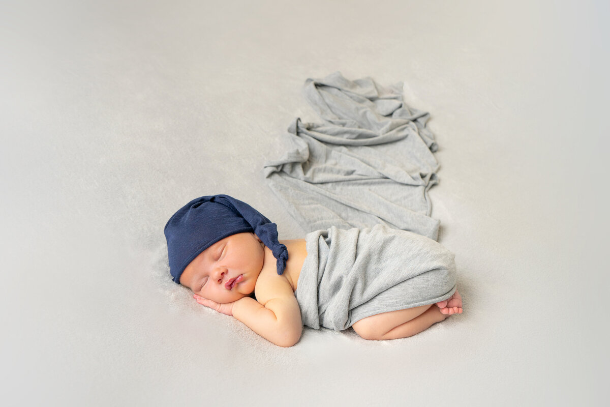 newborn-baby-wrapped-in-grey-with-blue-hat