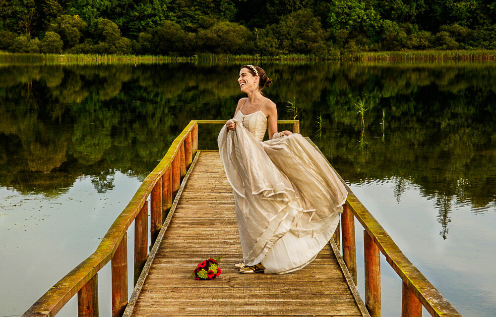 Bride with dark hair, wearing a leaf tiara and gold, boho style wedding dress and Gold Adidas trainers with colourful bouquet of flowers, while standing on a wooden jetty overlooking the lake at Castle Leslie Estate
