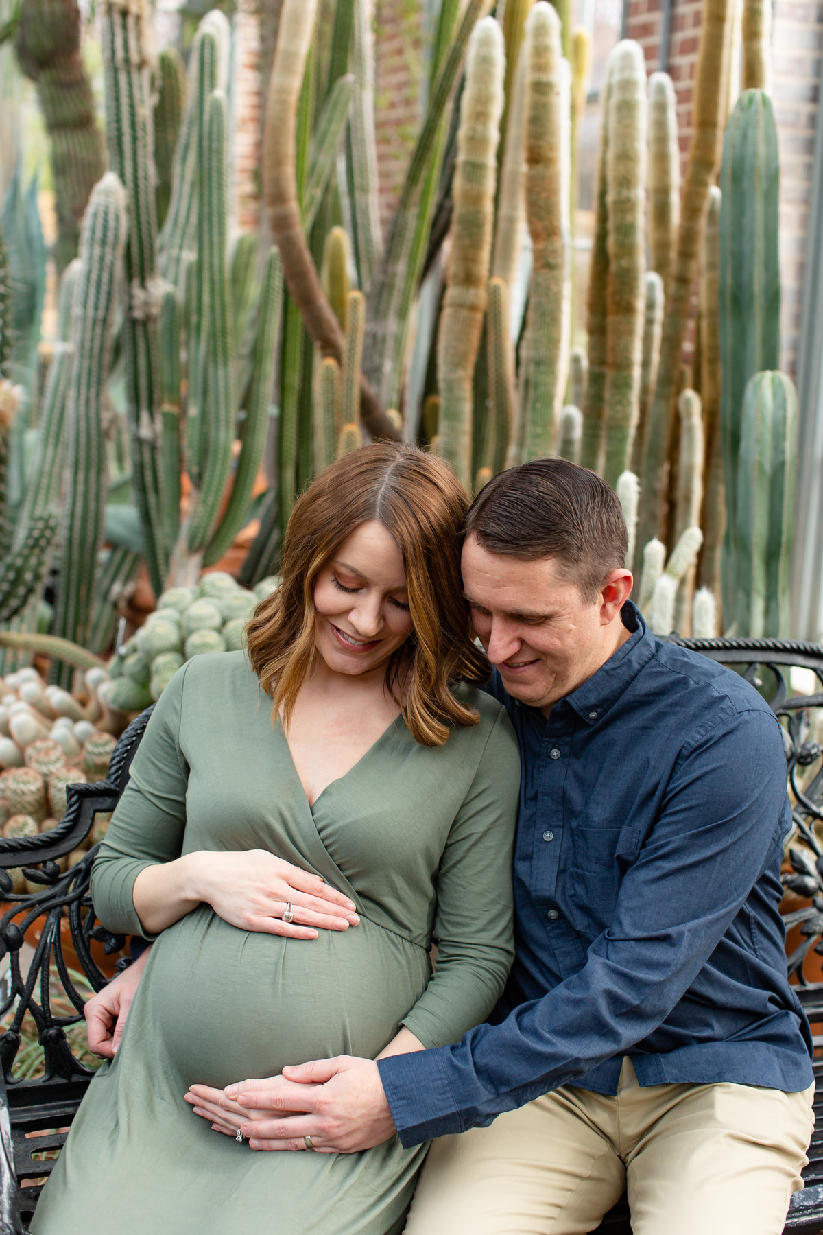 Winter Sunset Maternity Session with green maxi dress  sitting by cactus at Missouri Botanical Garden in St. Louis by Amy Britton Photography Photographer  in St. Louis