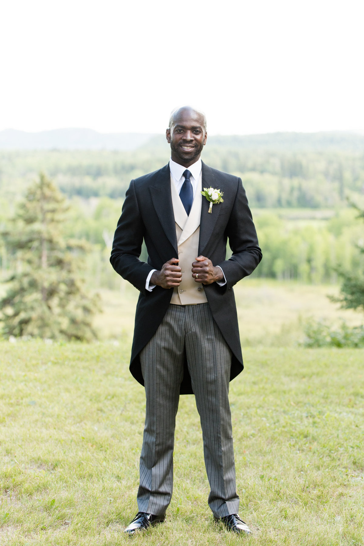 Groom poses for portrait during his summer wedding in Thunder Bay