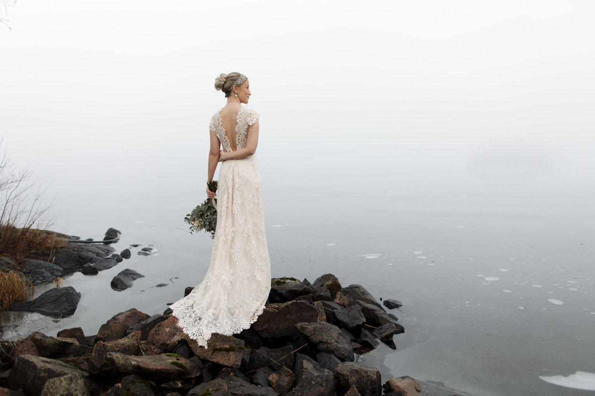 A bride standing on the stones by the water looking out on the mist