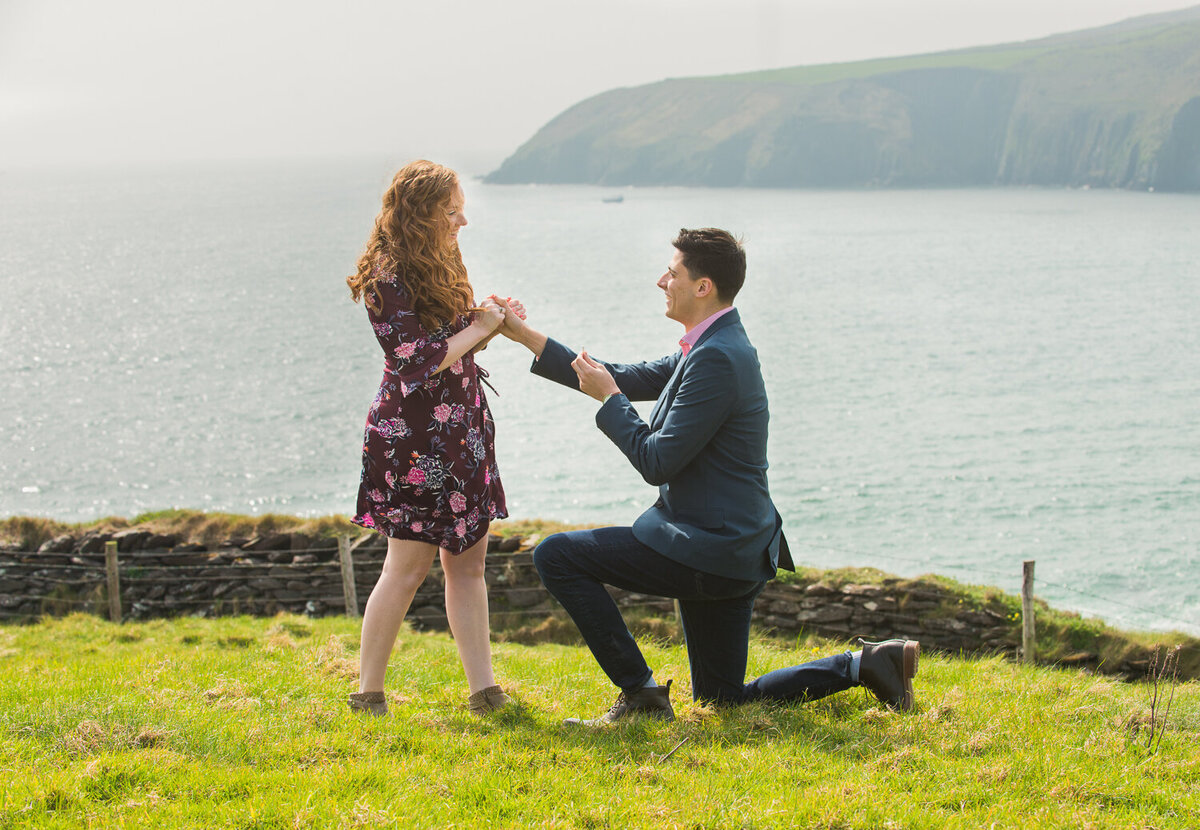 Young man going down on one knee to propose to his girlfriend in a field overlooking the sea