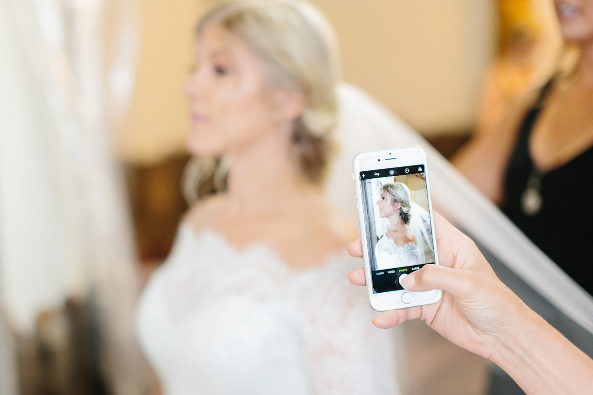 A woman with a cell phone taking a photograph.