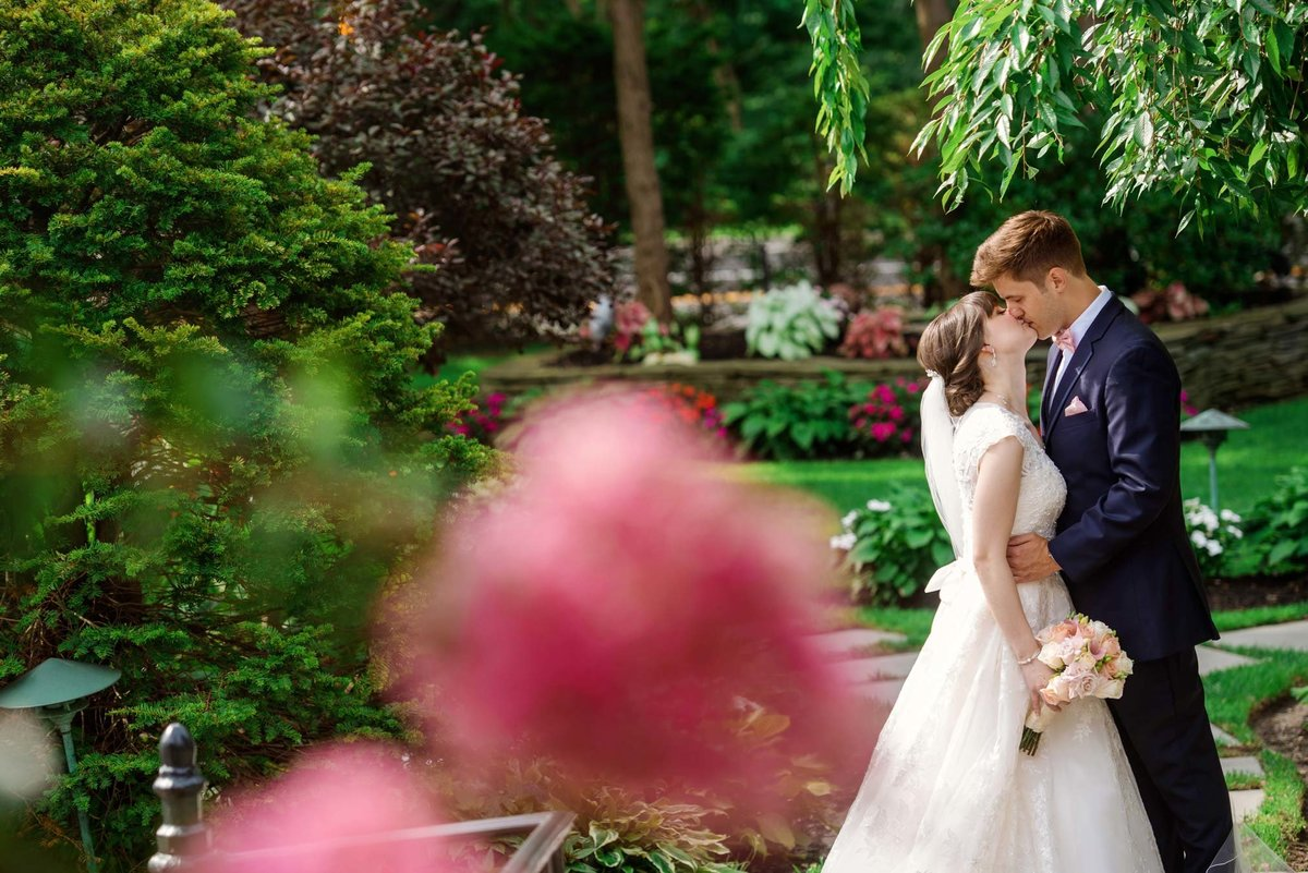 Bride and groom kissing at the gardens of Fox Hollow