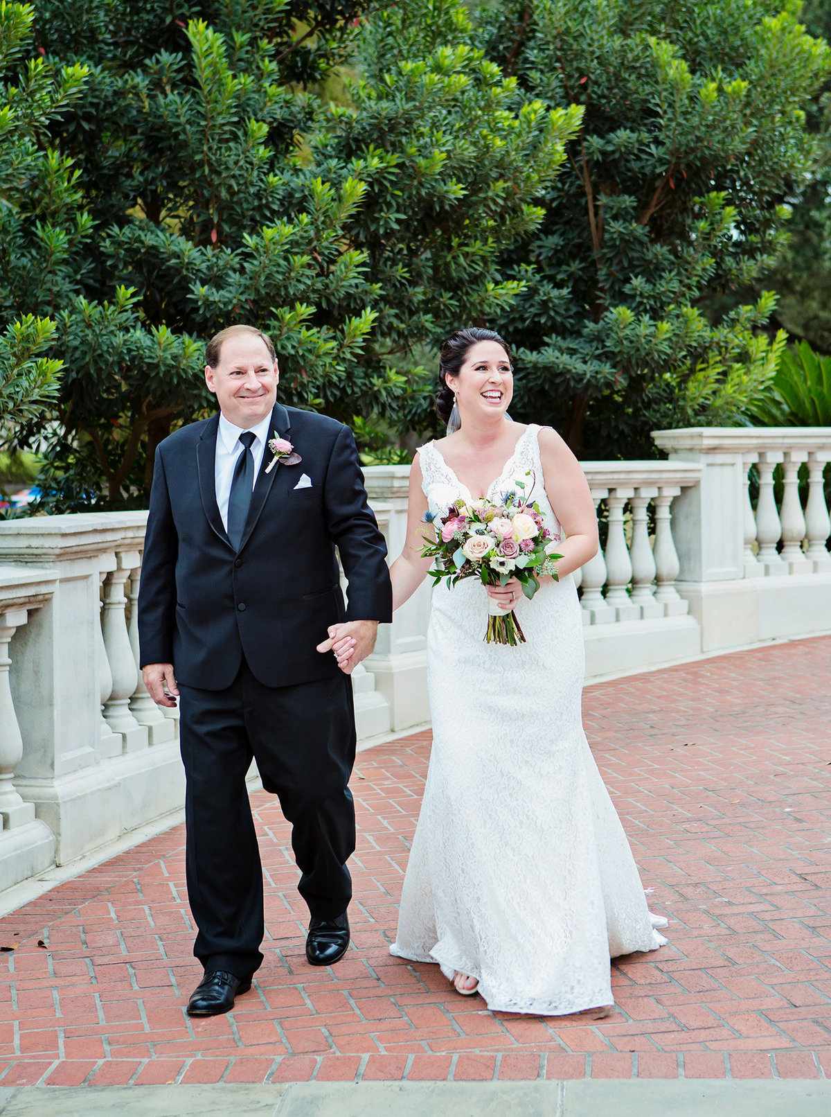 New Orleans bride smiling as she walks down the aisle with her Dad in Audubon Park