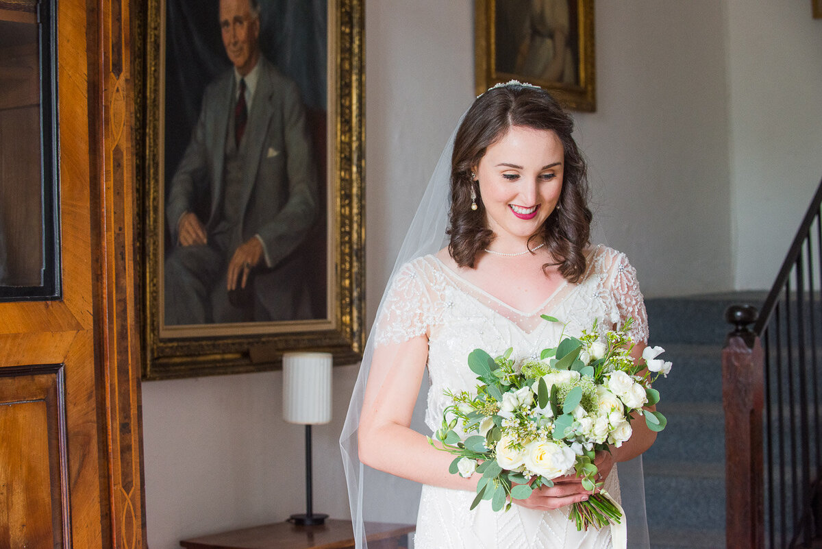 brunette bride wearing a vintage, empire style wedding dress looking at her white flower bouquet in the hallway of Westcove House, Kerry