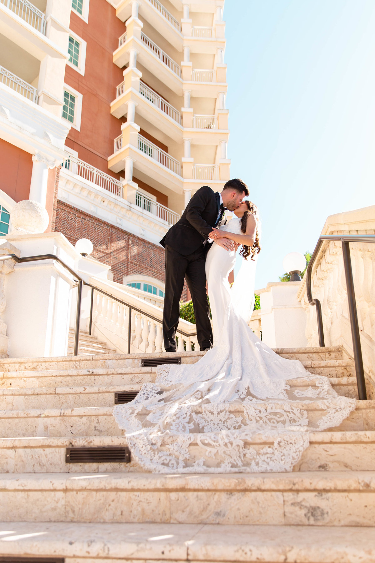 Bride and groom share kiss on marble staircase on their wedding day with bride in mermaid wedding dress with long lace train in Davenport, Florida