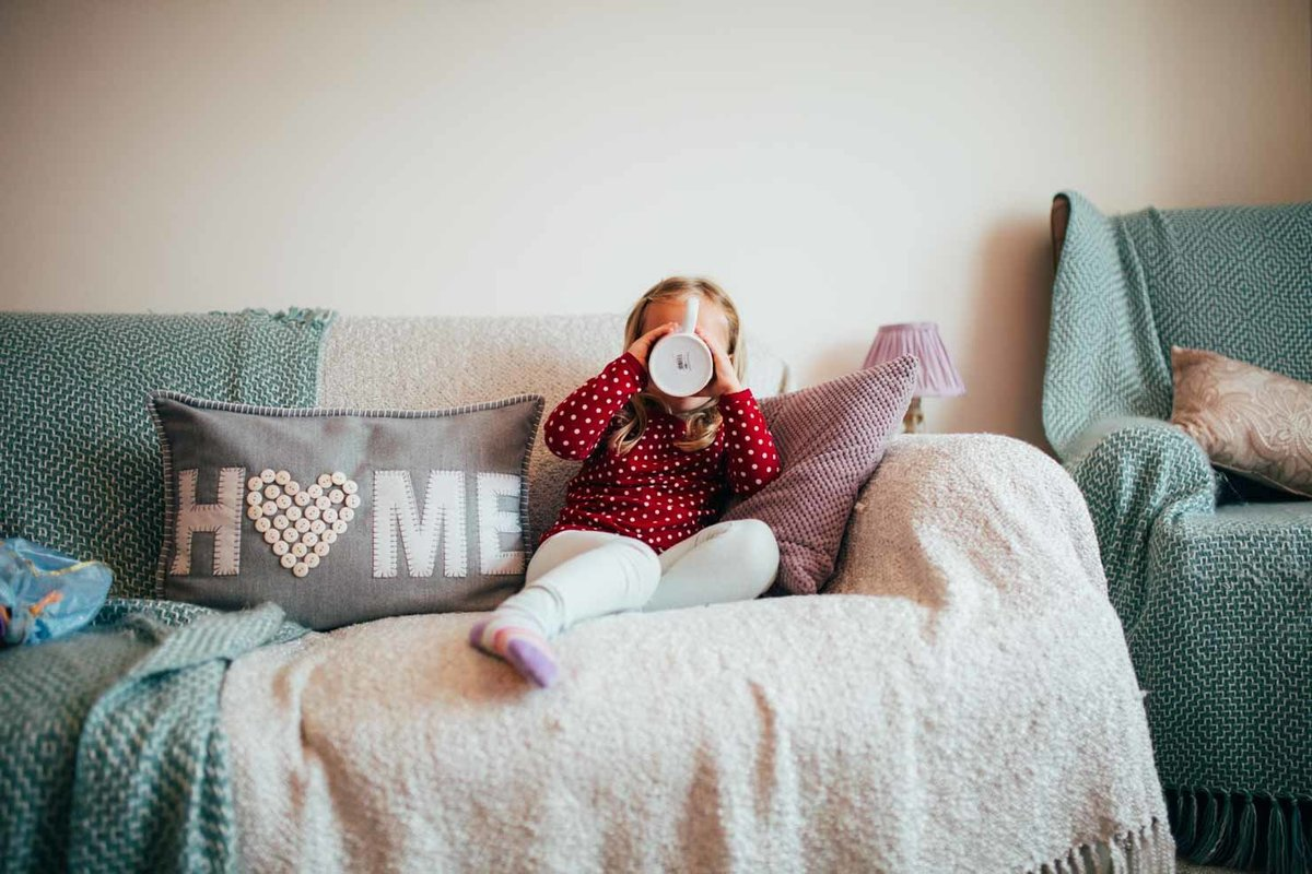 Candid photo of toddler drinking from a mug on the sofa in Ipswich, Suffolk