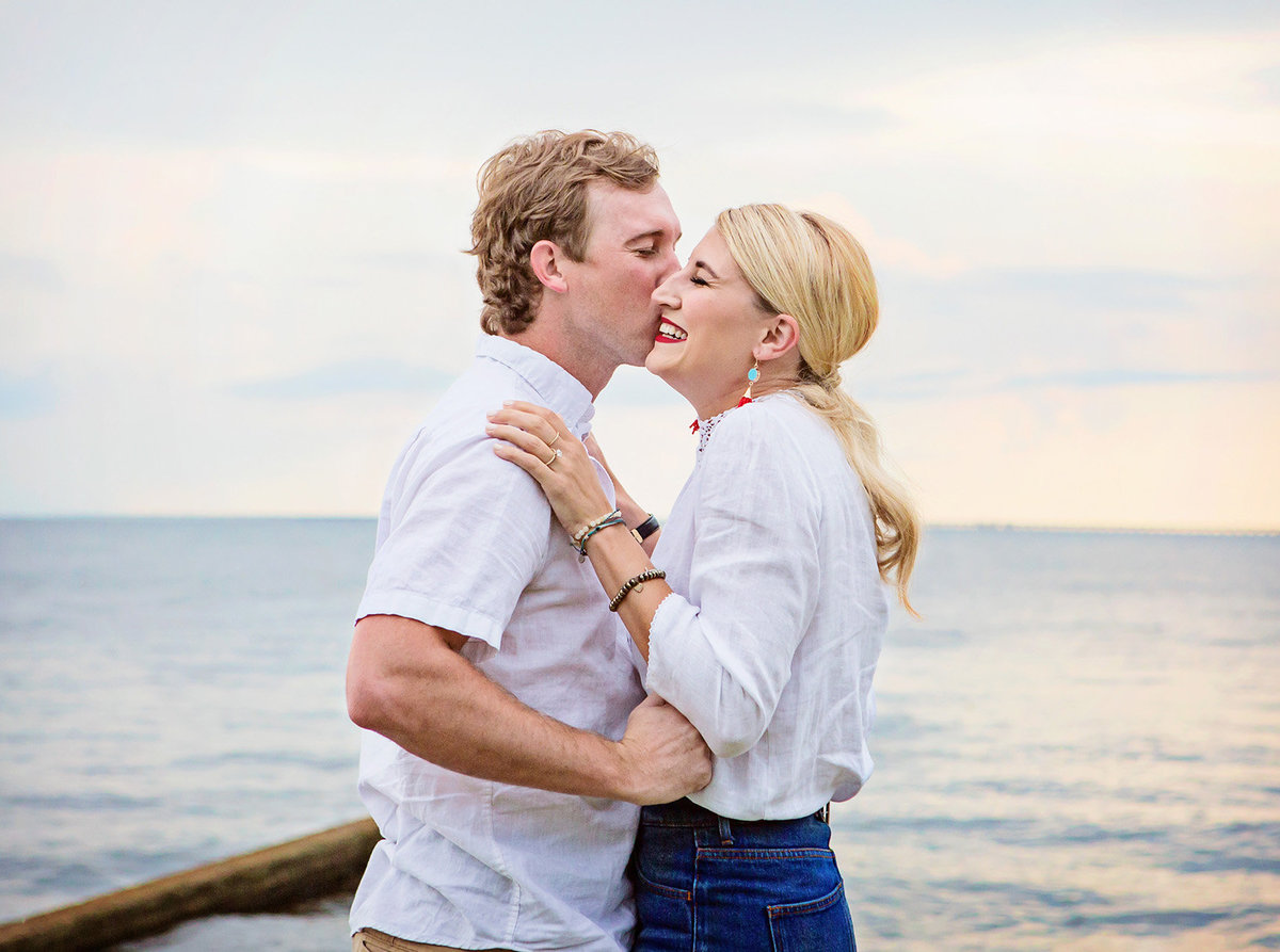 guy kissing fiancé after giving her engagement ring at Mandeville Lakefront