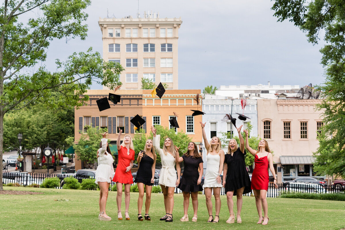 tri delta sorority seniors tossing graduation caps in downtown athens georgia