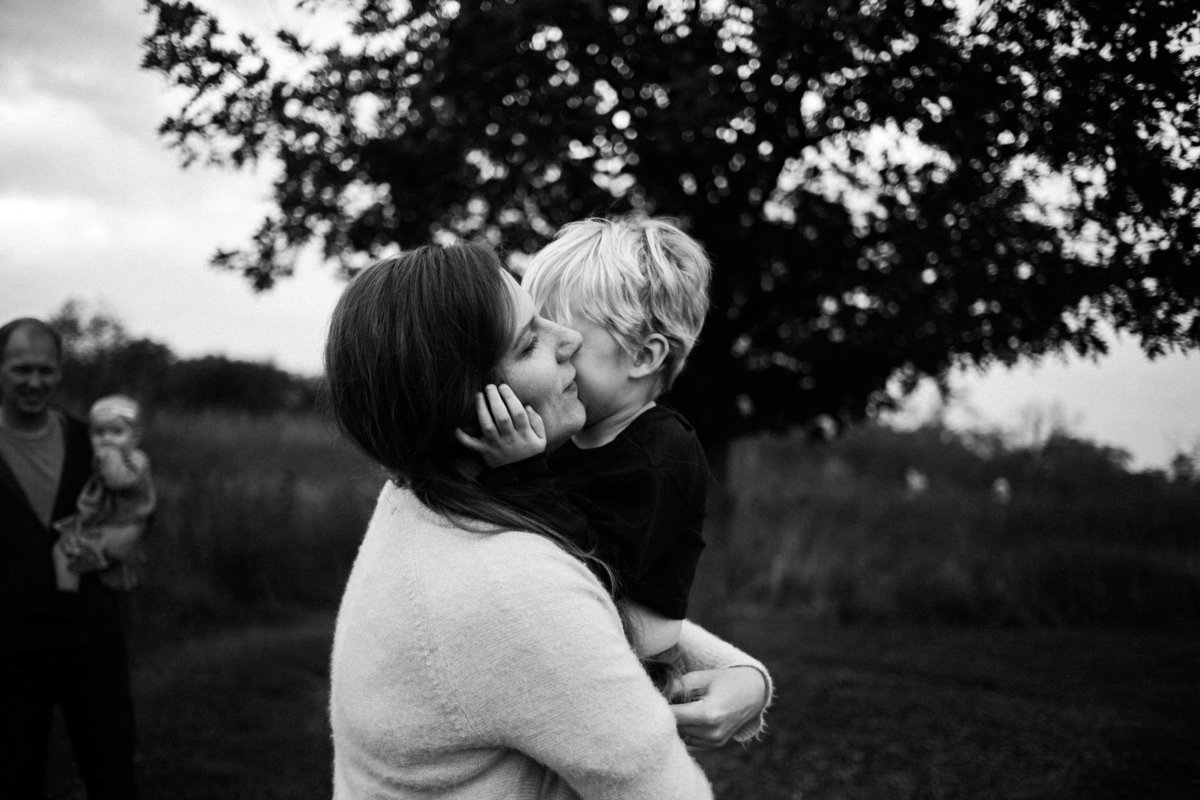 black and white image of a mother hugging and holding her blonde little boy in her arms