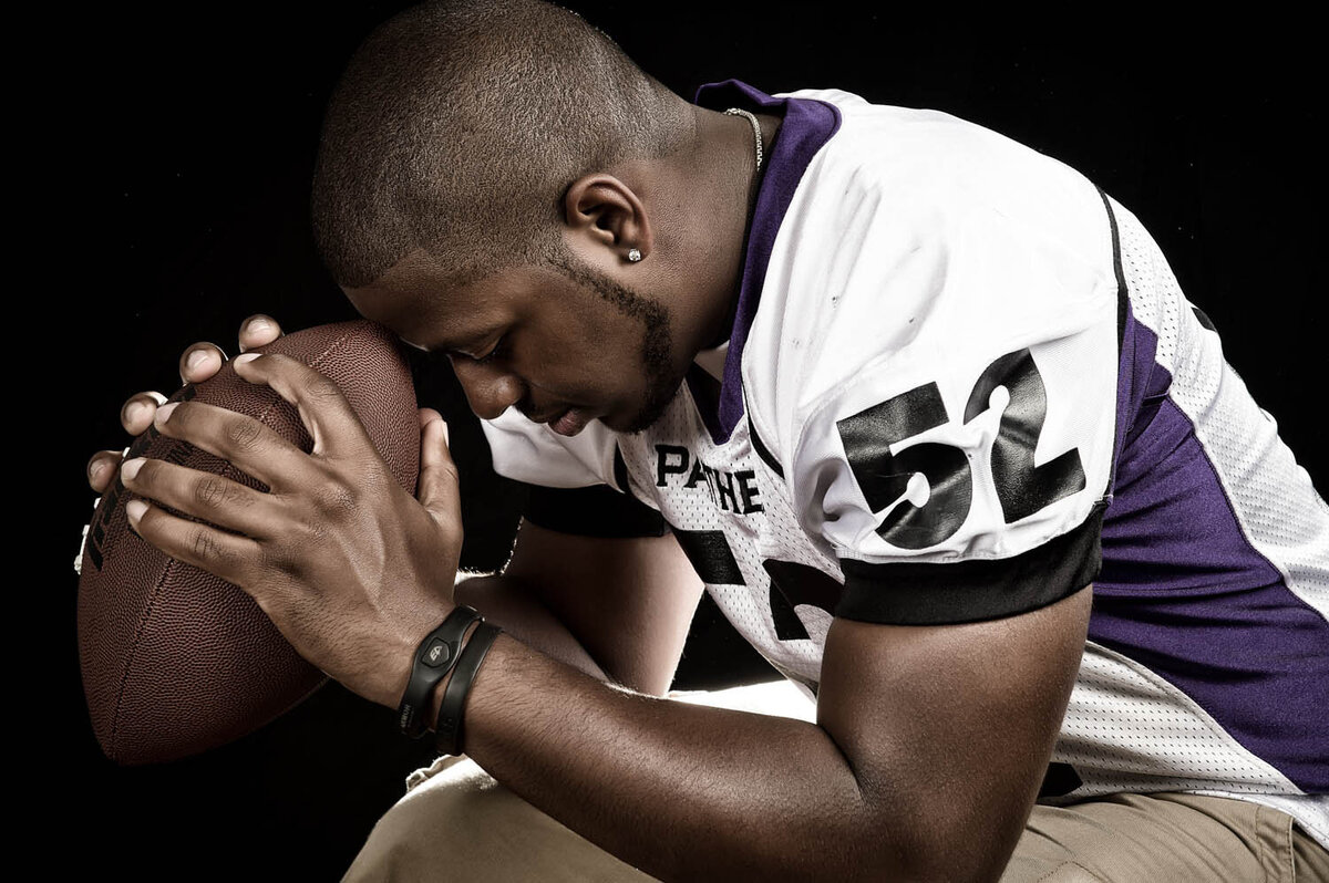 focus on football, senior with football, indoor studio