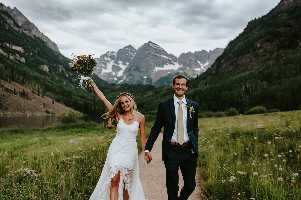 wedding couple being happy in front of the Maroon Bells in Aspen, CO