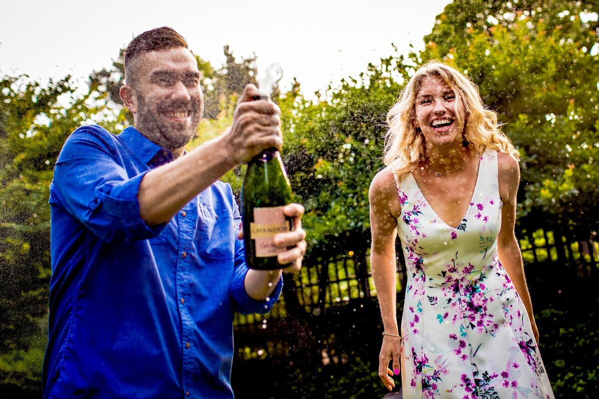 A couple sprays a bottle of champagne during a Garden of the Phoenix engagement session.