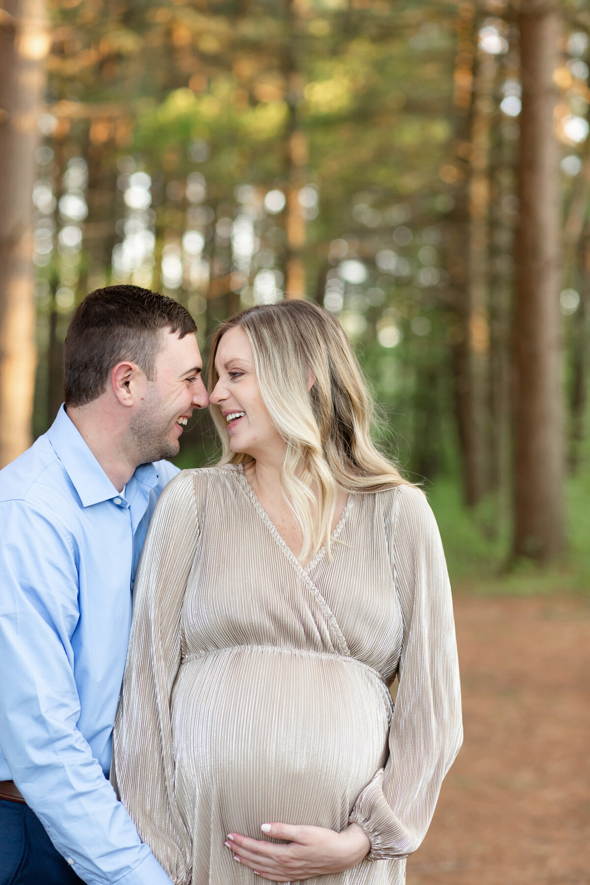 Spring Sunset Maternity Session with gold maxi dress standing by pine trees  at Busch Wildlife in St. Louis by Amy Britton Photography Photographer  in St. Louis