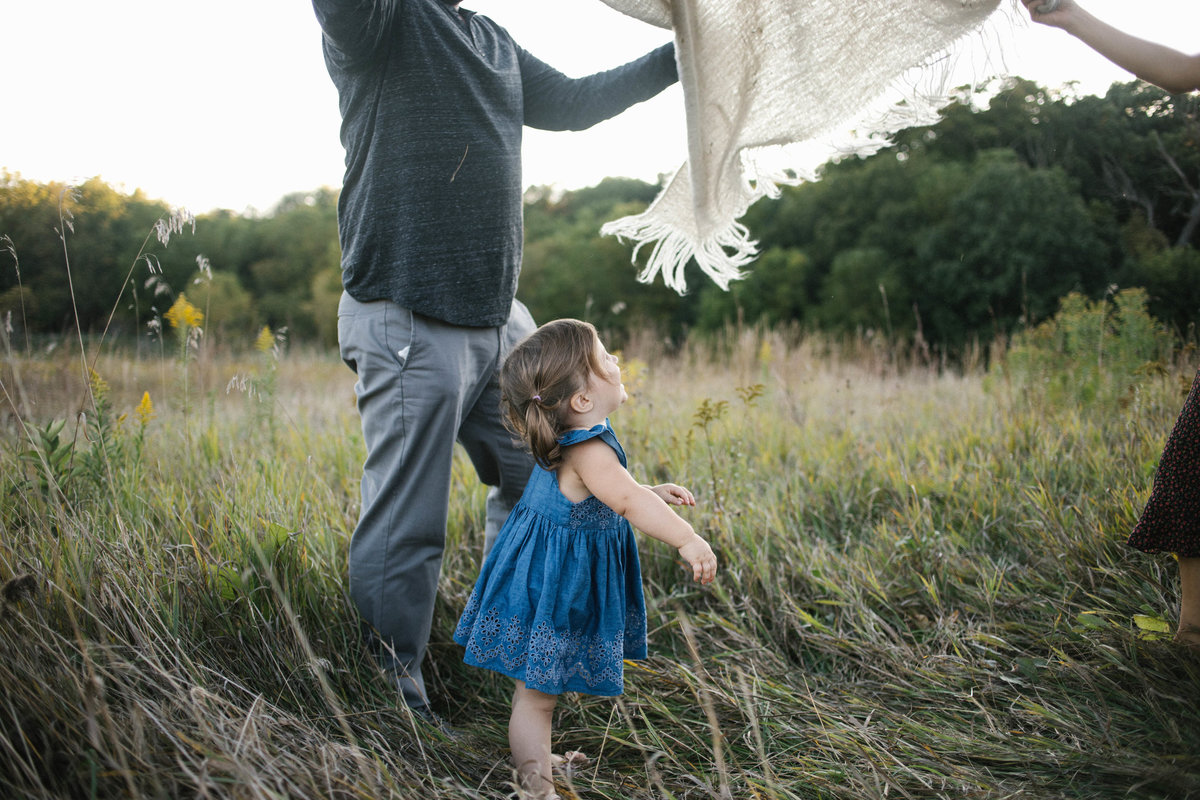 Parents playing peek a boo with little girl in a field