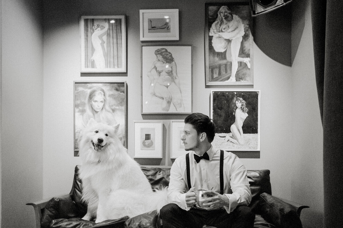 Man sitting with white fluffy dog in front of gallery wall black and white