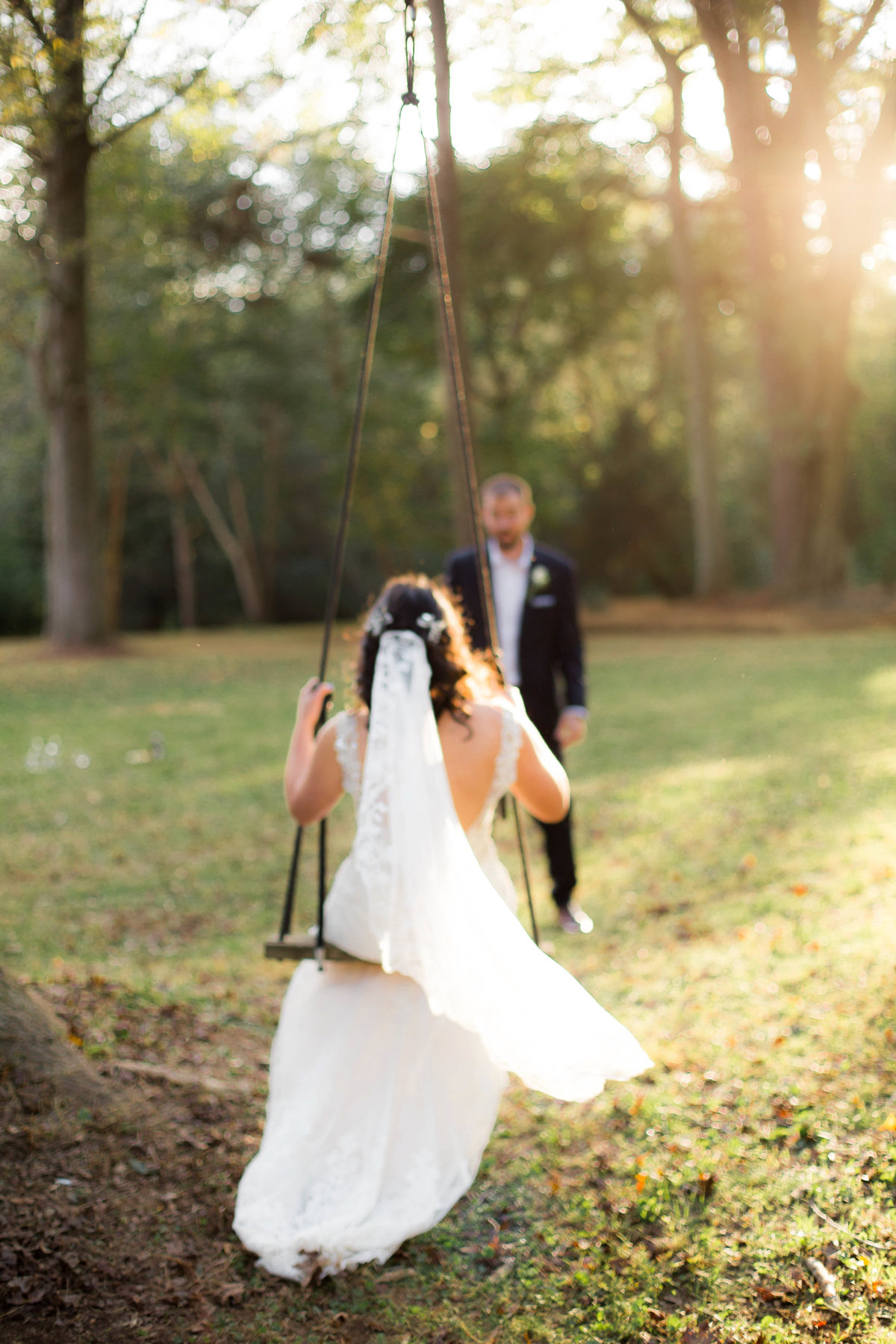 groom pushes bride on swing while sun shines down for wedding photographer