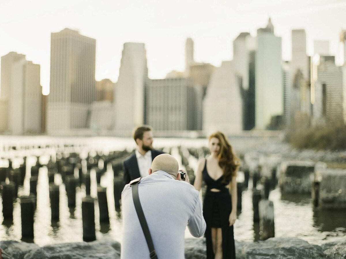 wedding photographer jeff brummett taking photo of couple standing in front of skyline at sunset NYC