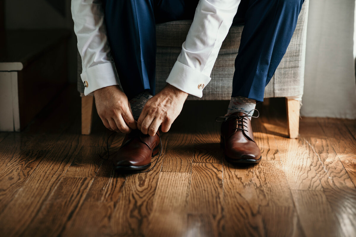 A picture of a closeup view of the groom leaning over to tie his shoes as he finishes getting dressed for his wedding ceremony by Garry & Stacy Photography Co - Bradenton wedding photographer