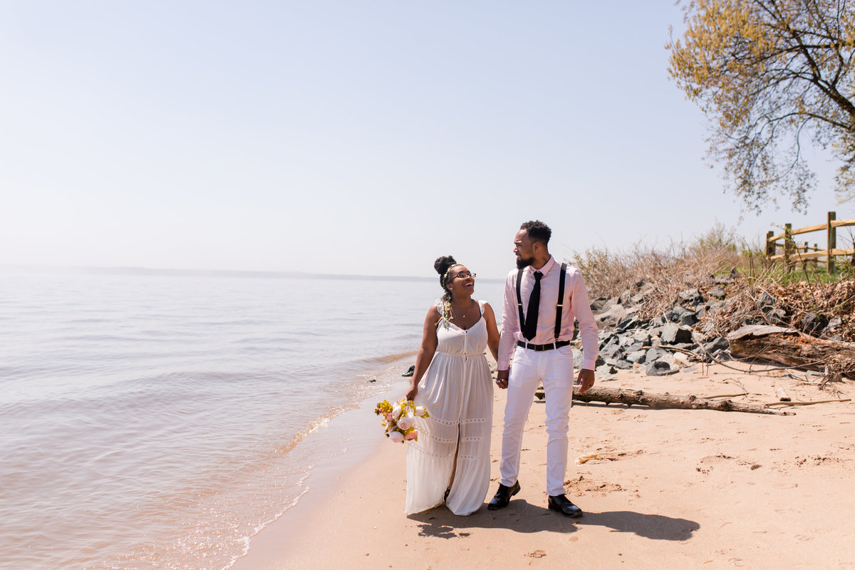 A bride and groom walking along the beach at Leesylvania Park