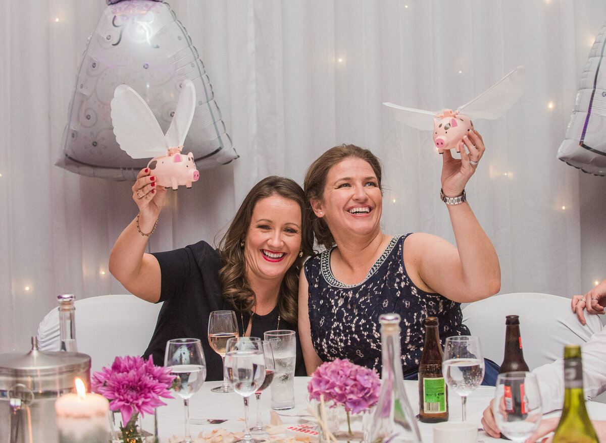 Gay brides posing with flying pigs at wedding reception