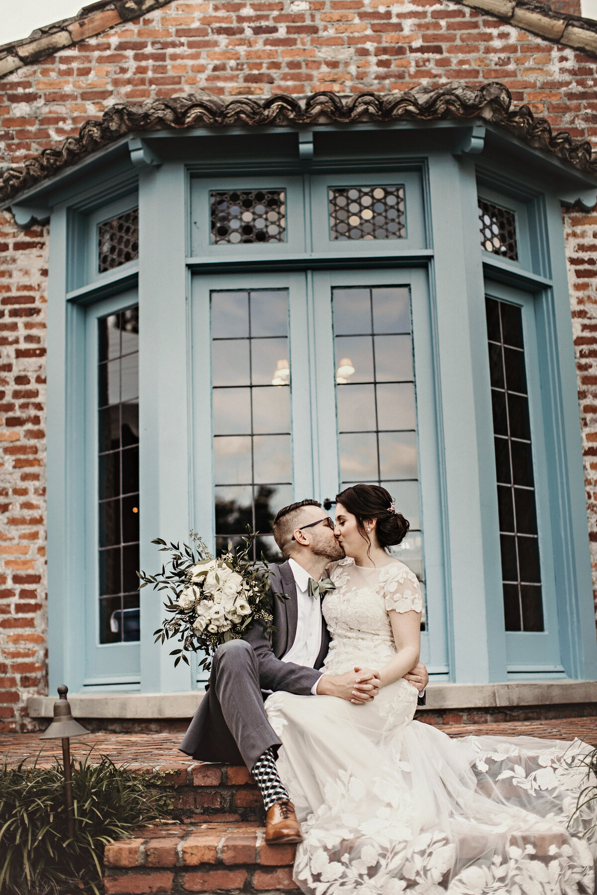 A photograph of the bride and groom embracing and tenderly kissing as they sit on brick steps, showing the bride's train spread out, in front of a picturesque vintage window by Garry & Stacy Photography Co - Clearwater Florida wedding photography