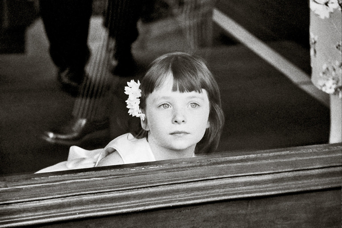 A flowergirl peering outside at a wedding in San Francisco.