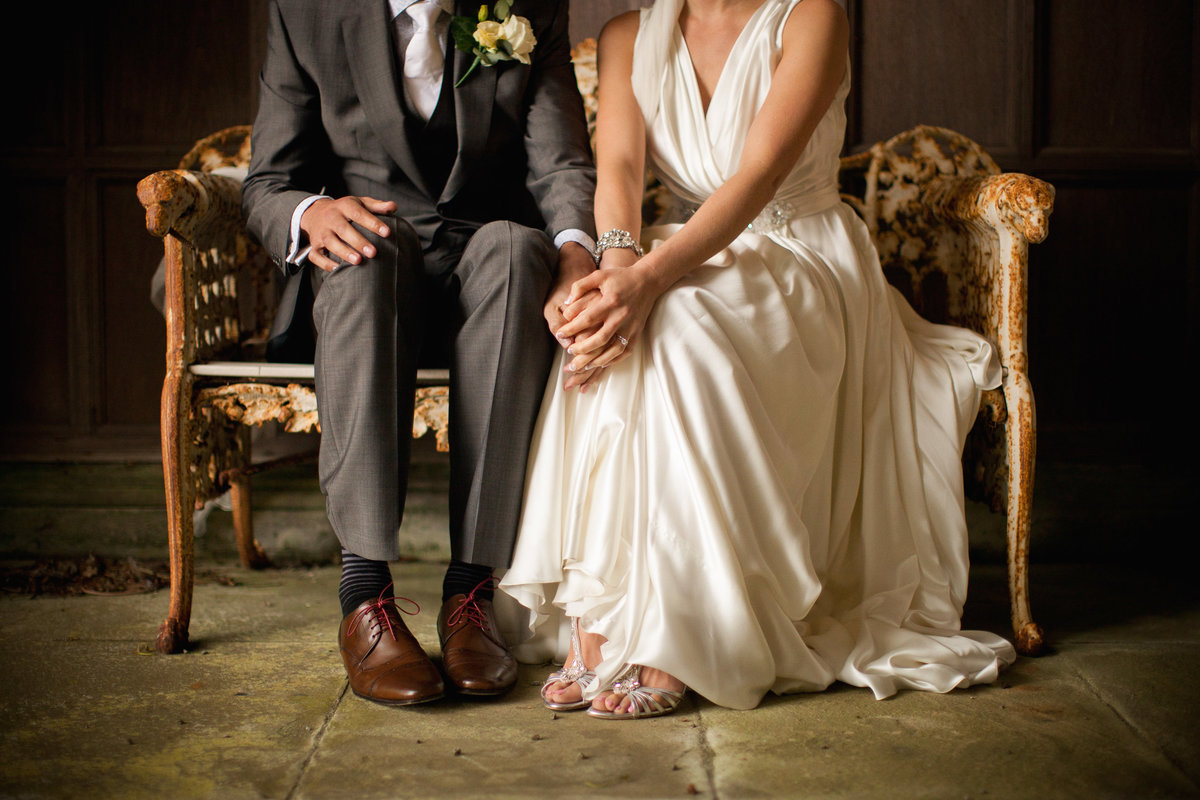 closeup of bride and groom with silk wedding dress at thornton manor on a bench