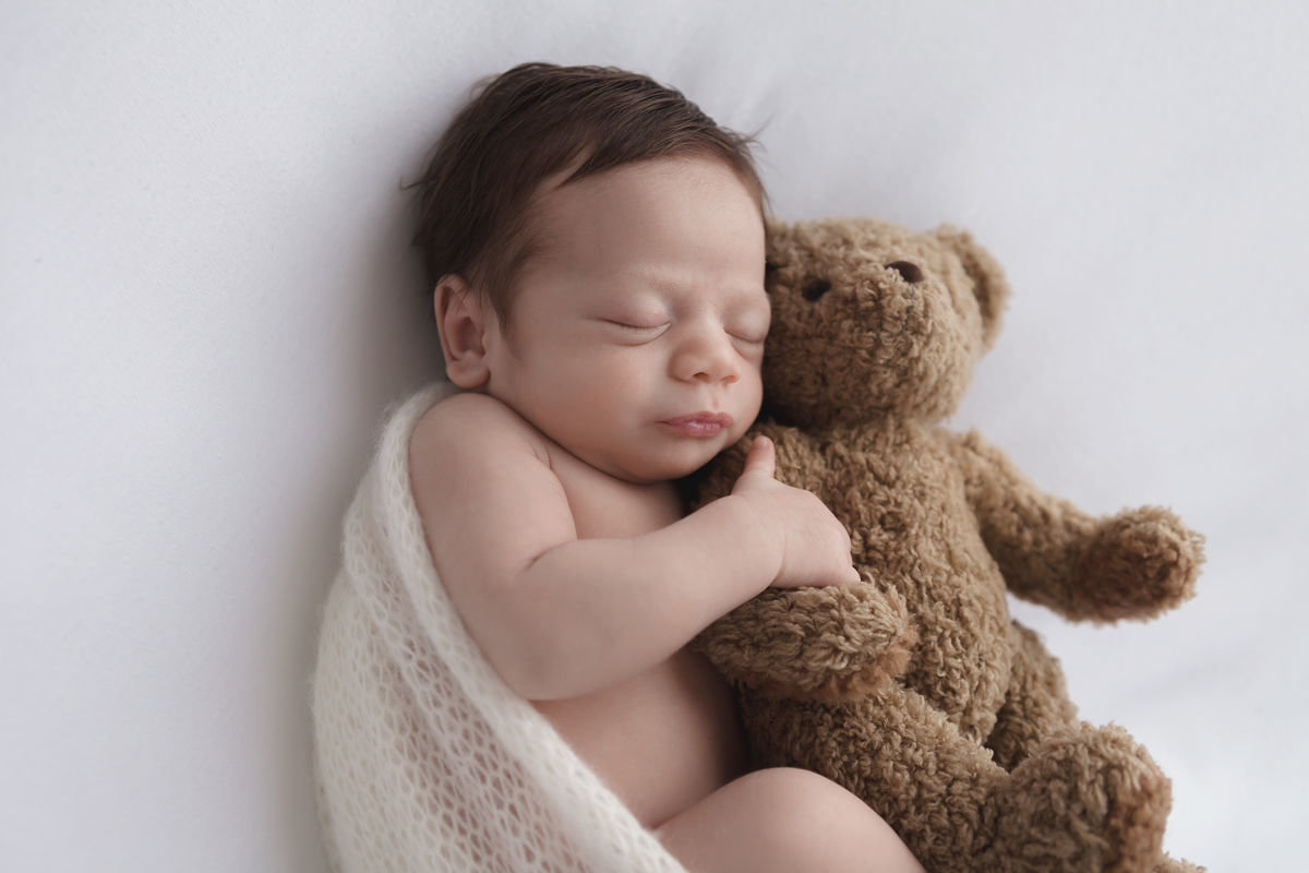 baby boy hugging a bear on white background