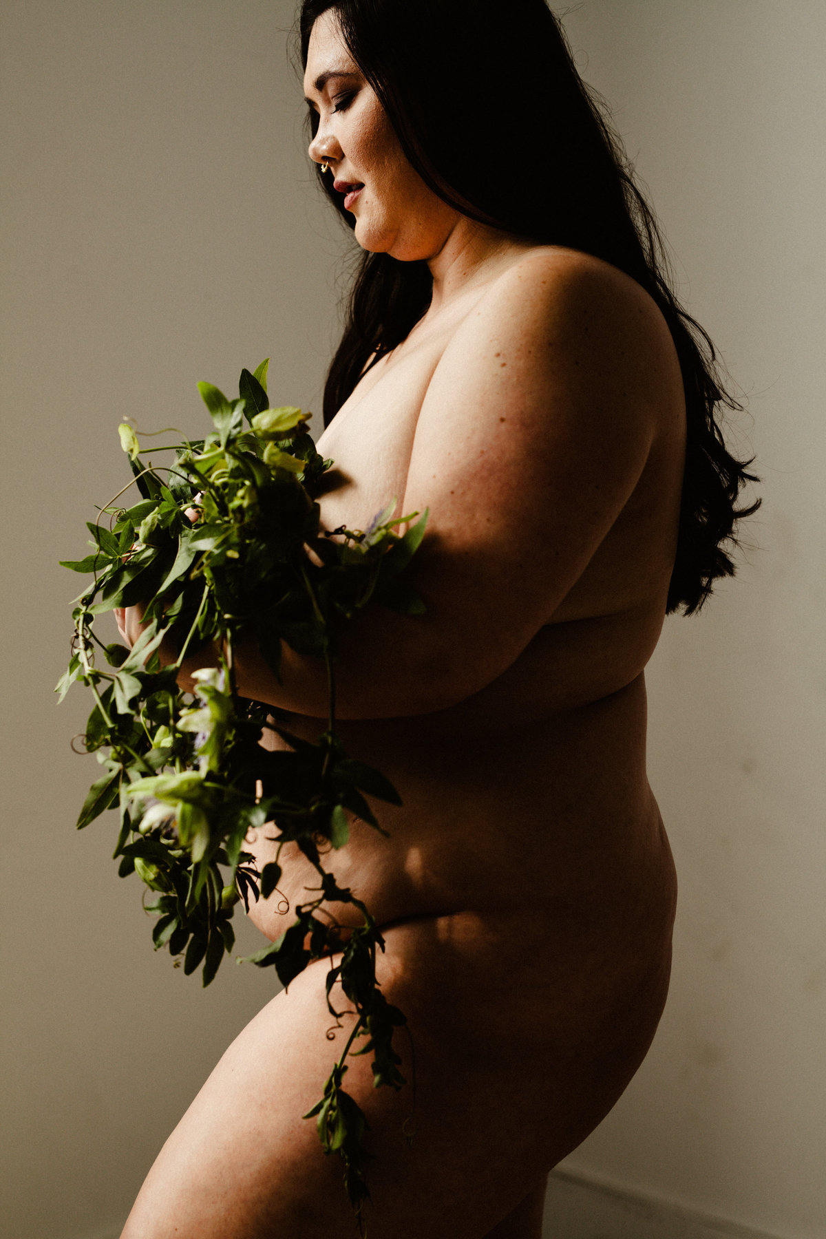 nude woman holds greenery arrangement in her arms